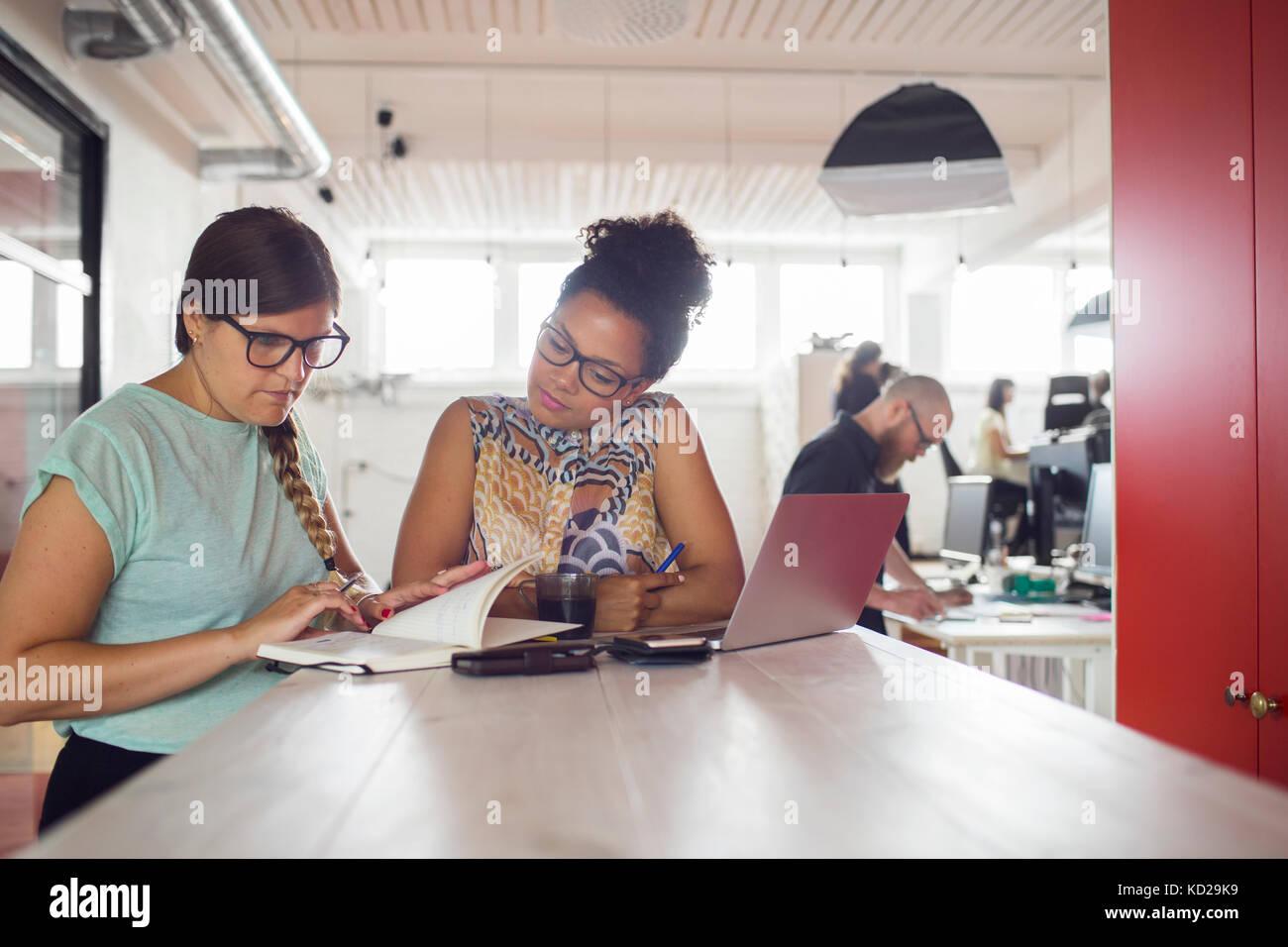 Las mujeres que trabajan por la tabla en la oficina, sus compañeros de trabajo en segundo plano. Foto de stock