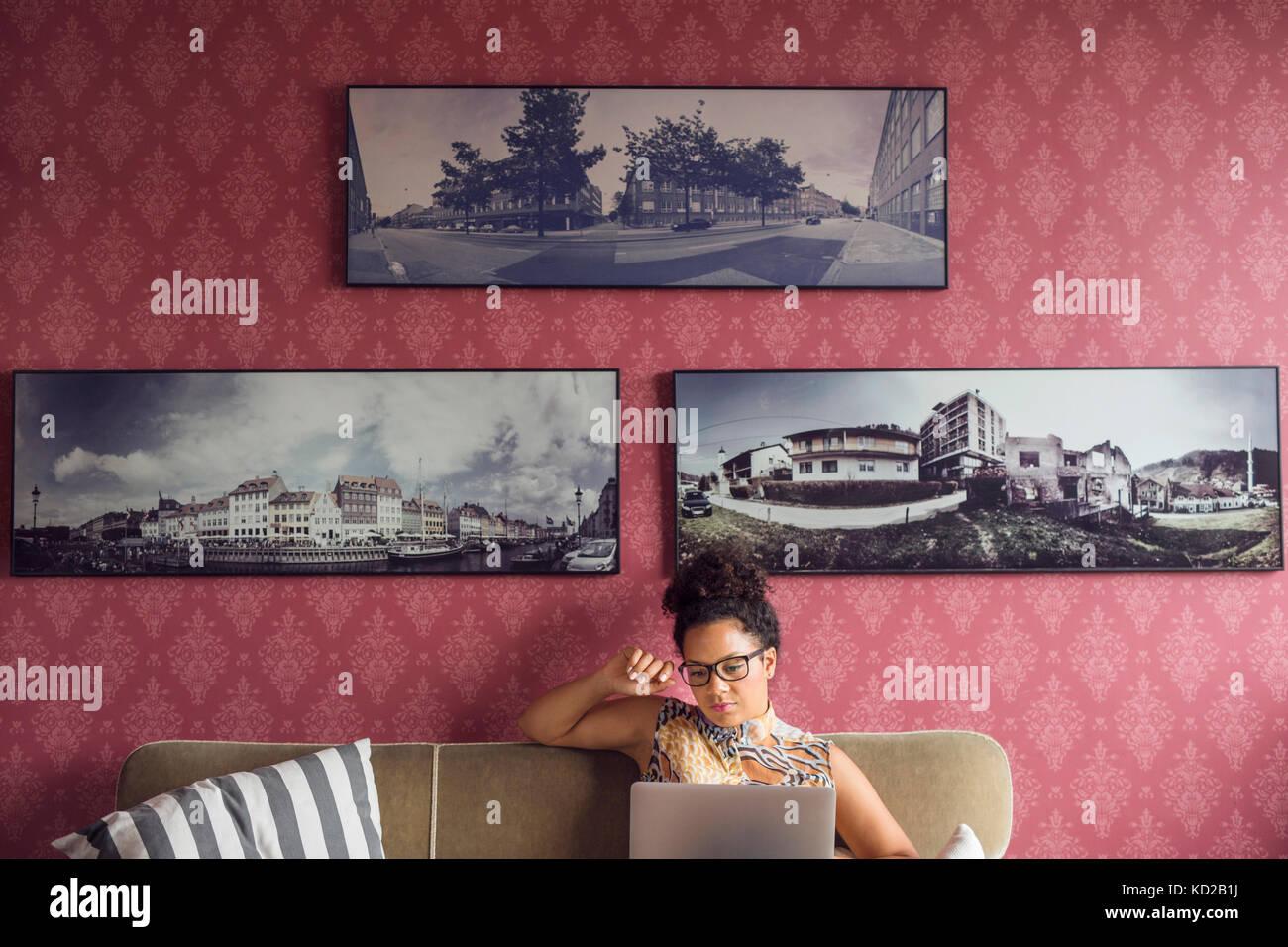 Hermosa mujer sentada en un sofá y utilización portátil Foto de stock