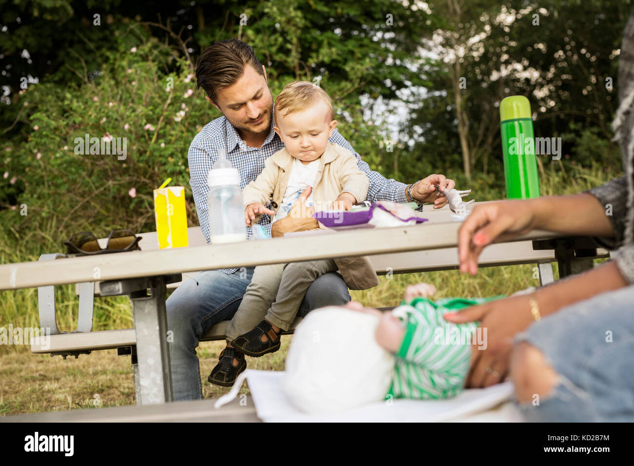 Padre sentado con mi hijo (18-23 meses) por mesa de picnic Foto de stock