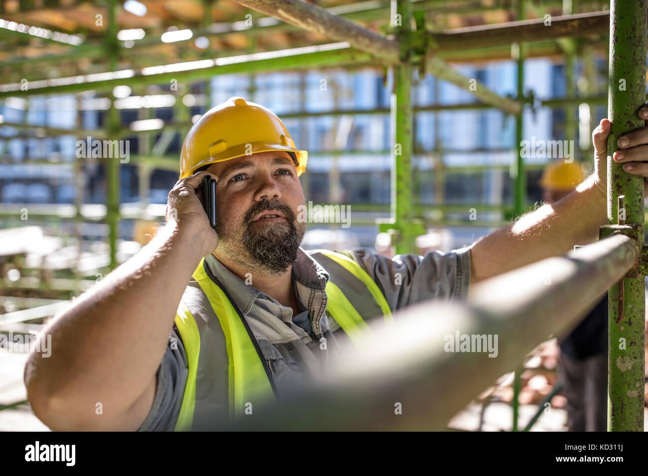Trabajador de la construcción a través de teléfono móvil Foto de stock