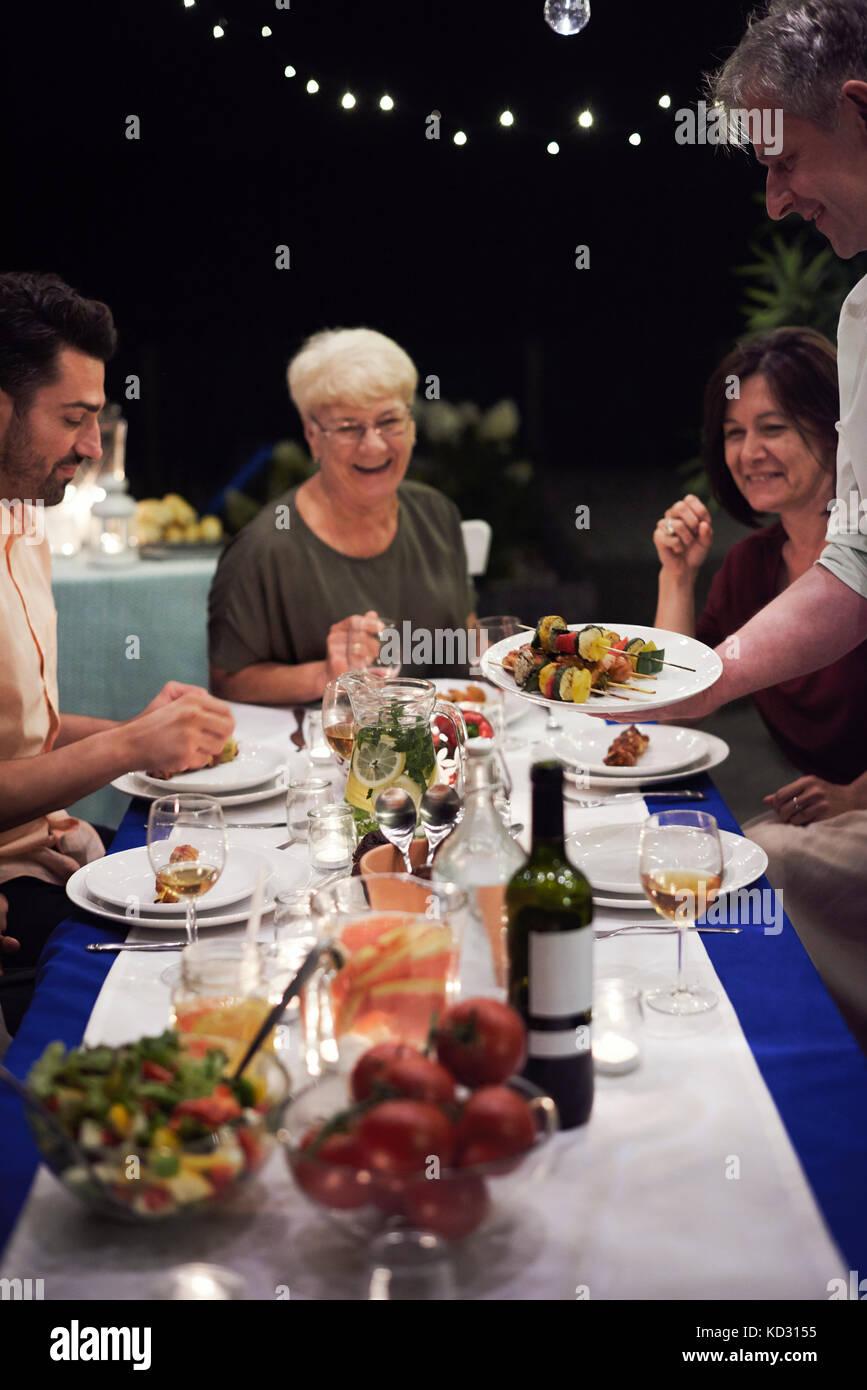 Grupo de gente sentada en la mesa, disfrutando de comida Foto de stock
