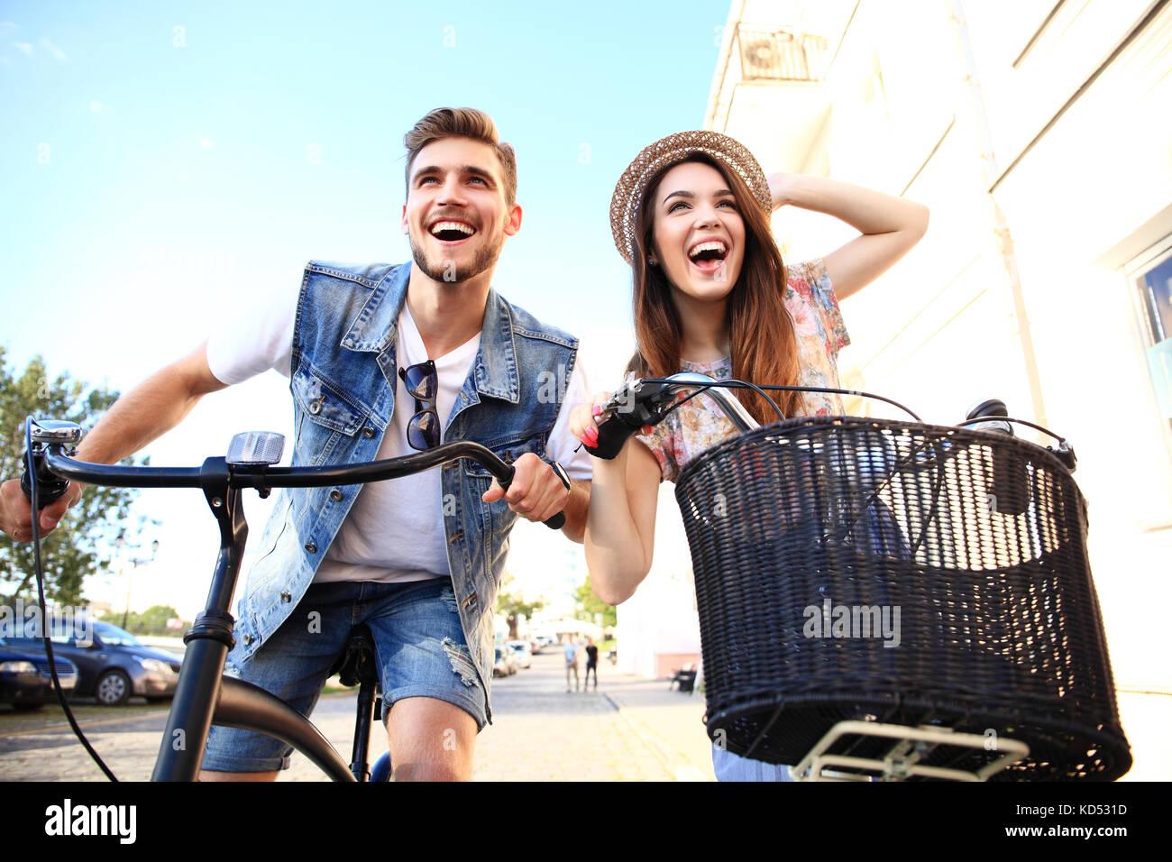 Feliz pareja joven va para un paseo en bicicleta en un día de verano en la ciudad.se divierten juntos. Imagen De Stock
