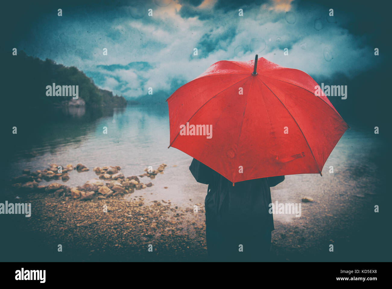 Mujer con sombrilla roja contempla la lluvia delante de un lago. triste y solitaria persona femenina mirando a distancia. Imagen De Stock
