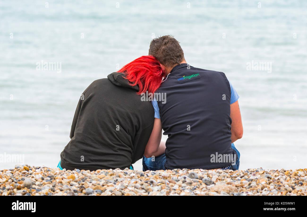 Pareja joven sentado en la playa al lado del mar, compartiendo un momento. Foto de stock