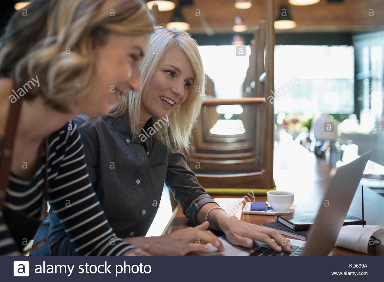 Los dueños de negocios Cafetería femenina trabaja en equipo portátil Imagen De Stock