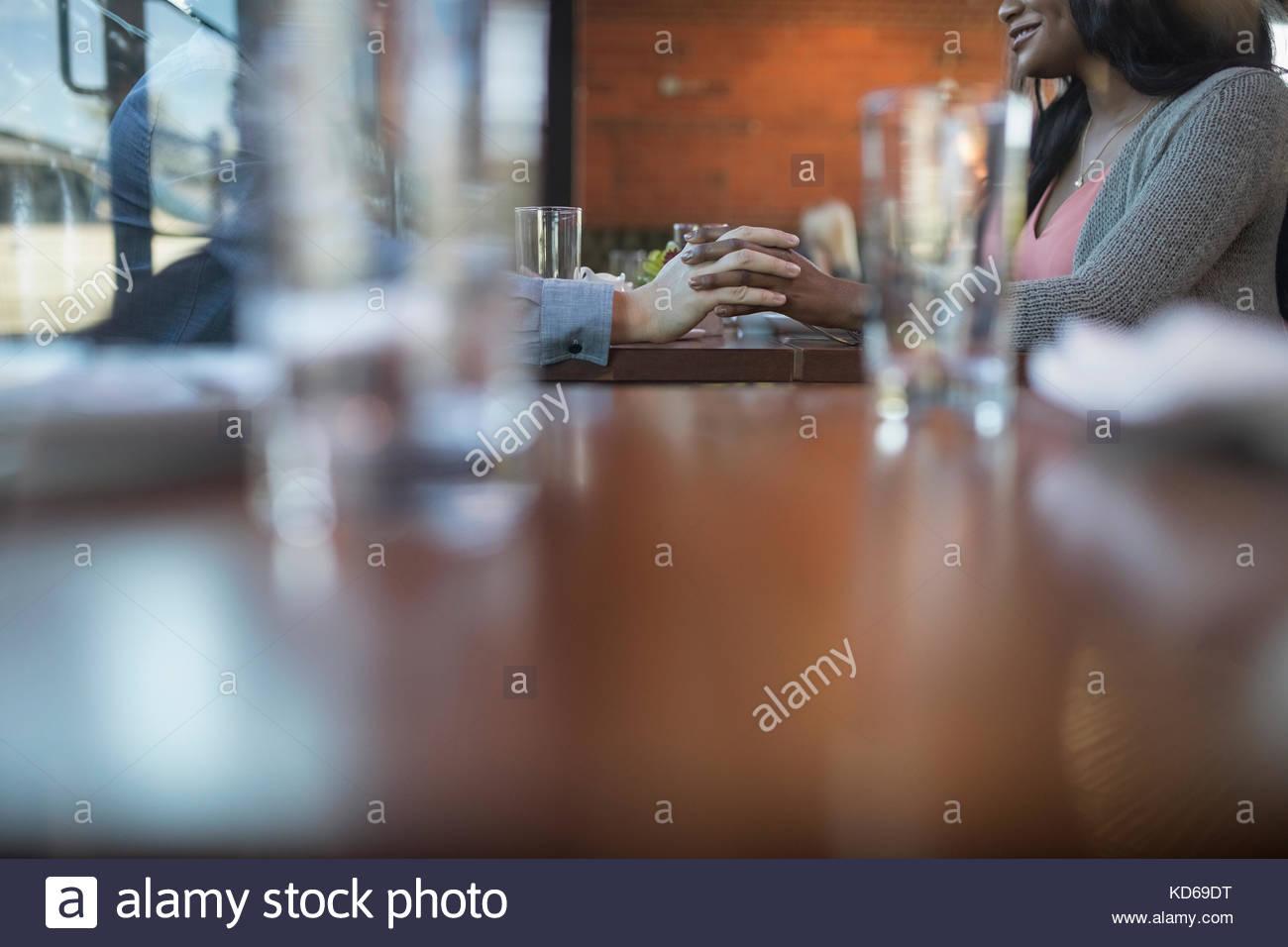 Afectuosa pareja tomados de las manos, para cenar en el restaurante table Imagen De Stock