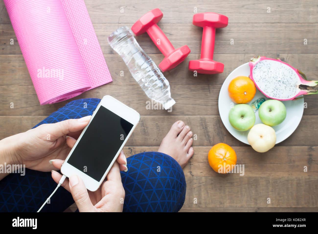 48fb9c4c Mujer saludable mediante smartphone antes de entrenar y yoga ...