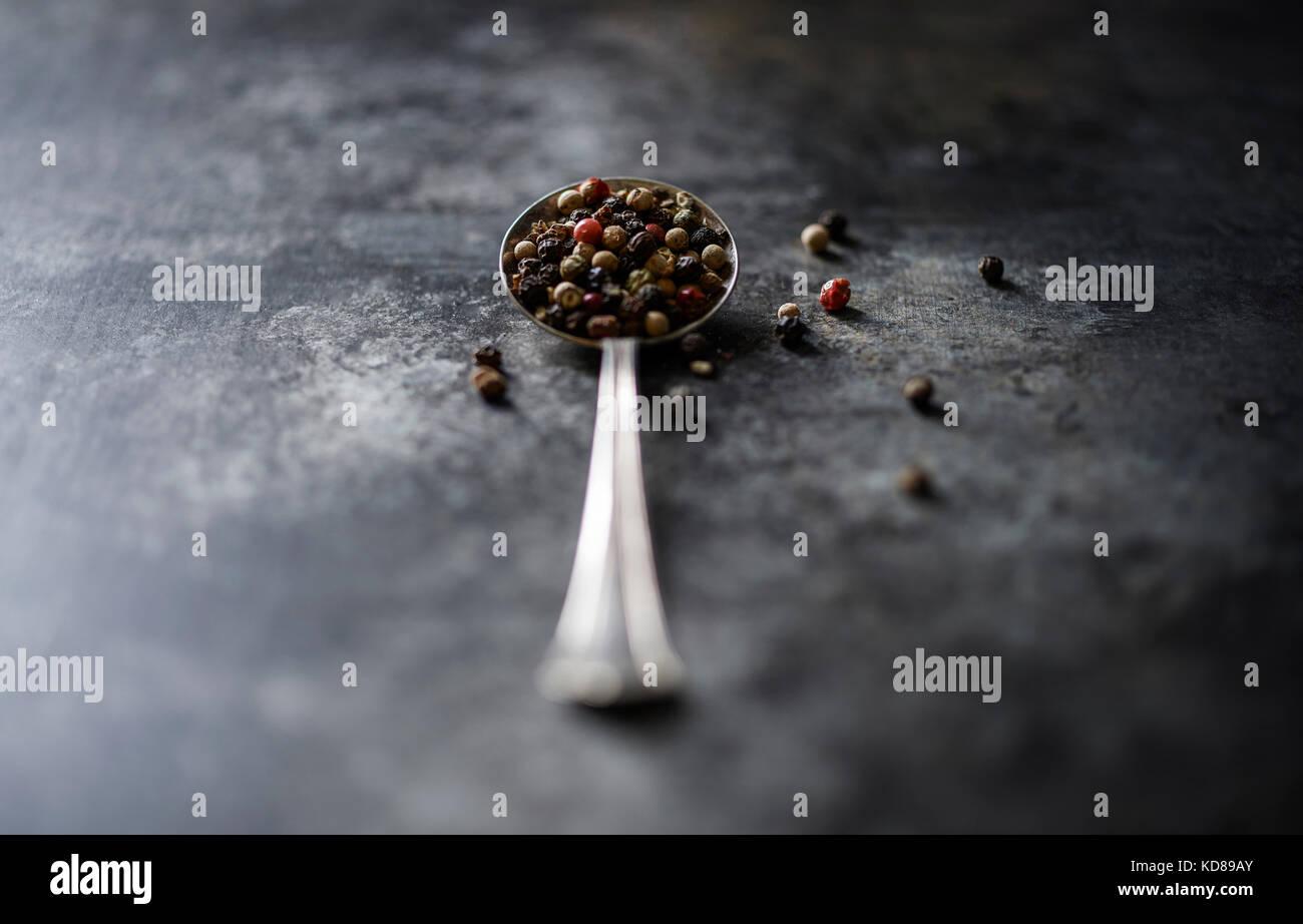 Un vintage cuchara llena de hermosos pimienta tricolor en una oscura superficie rústica. Imagen De Stock
