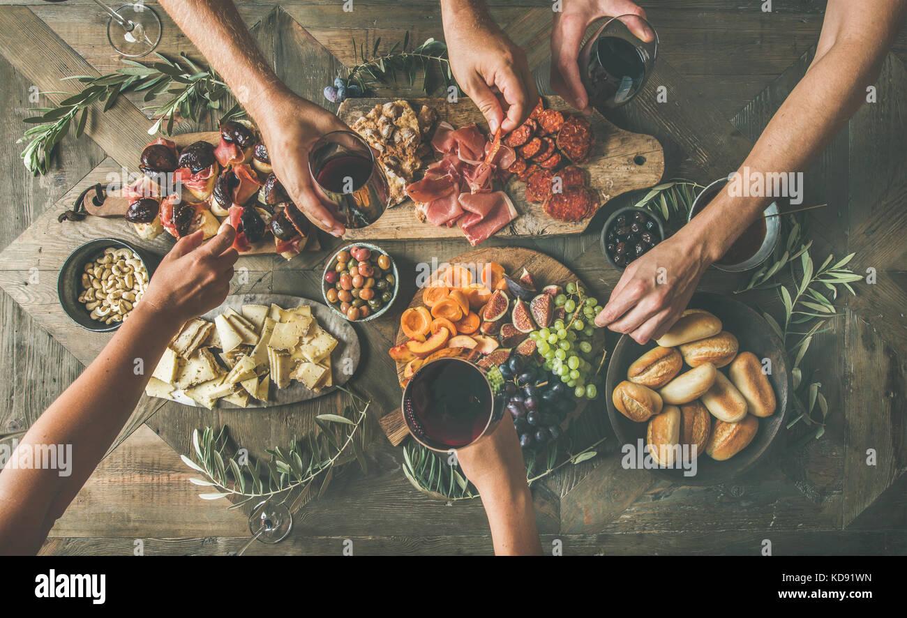 Vista superior de gente bebiendo, comiendo juntos y manteniendo las gafas Imagen De Stock