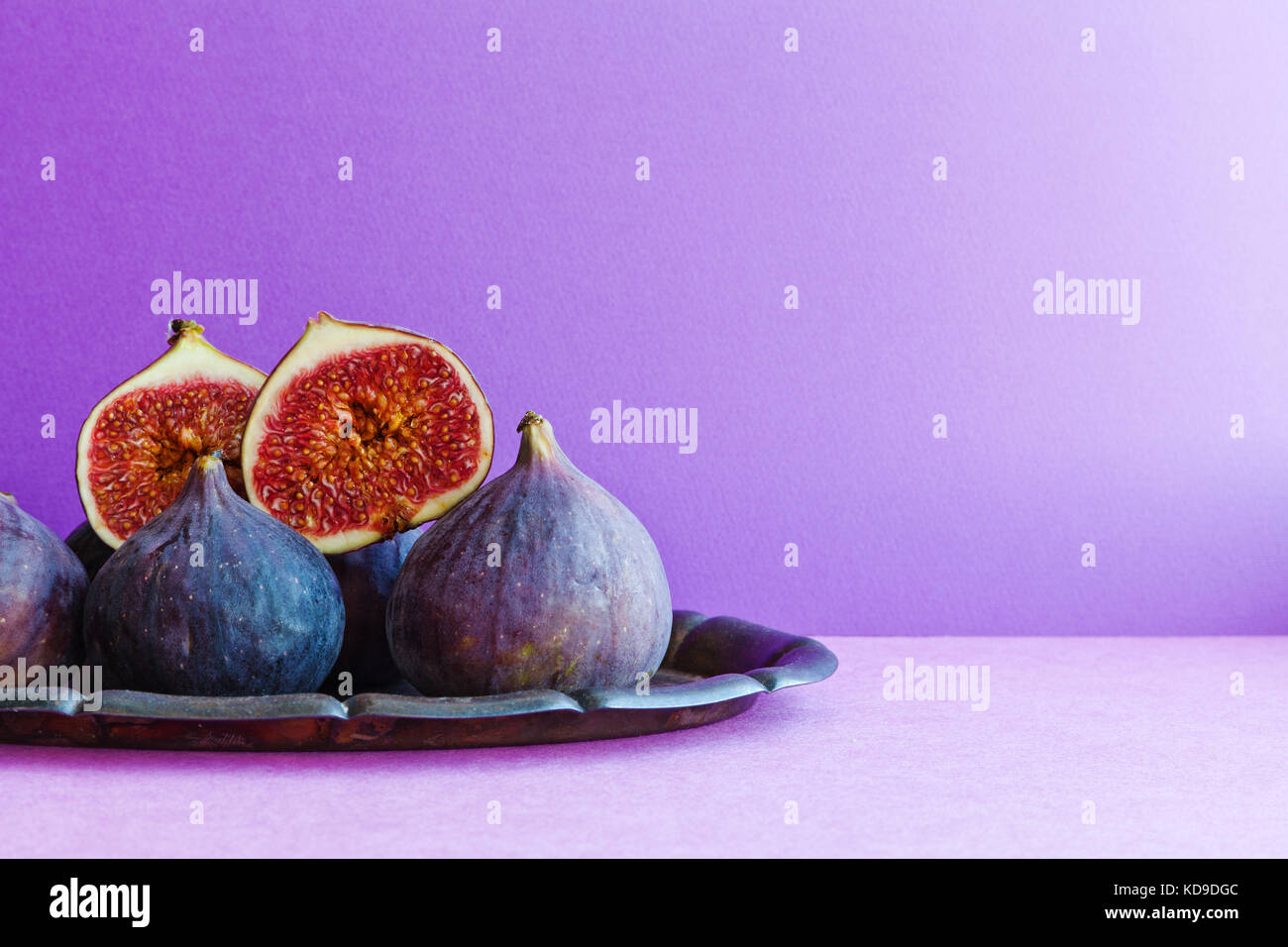 Todavía brillante vida fig frutas orgánicas en una antigua bandeja, hermoso fondo violeta púrpura. Imagen De Stock