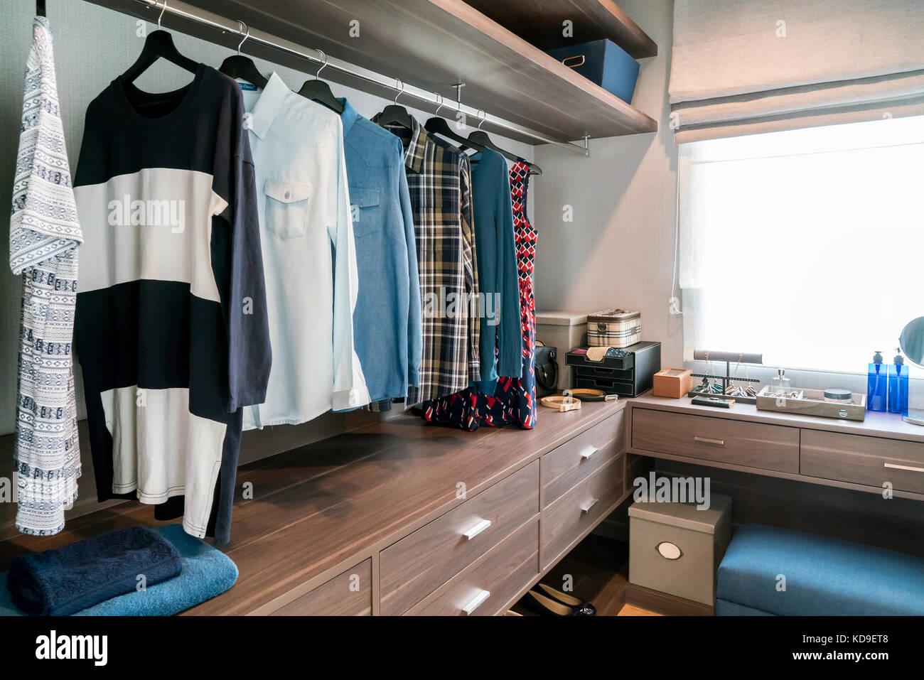 Habitación con estantes de madera y vestidos colgando debajo del bastidor 8303377a502