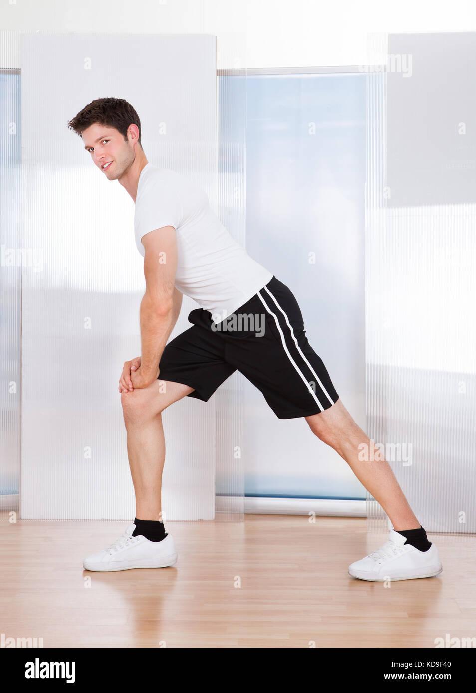 Foto de joven apuesto hombre haciendo ejercicios de estiramiento Imagen De Stock