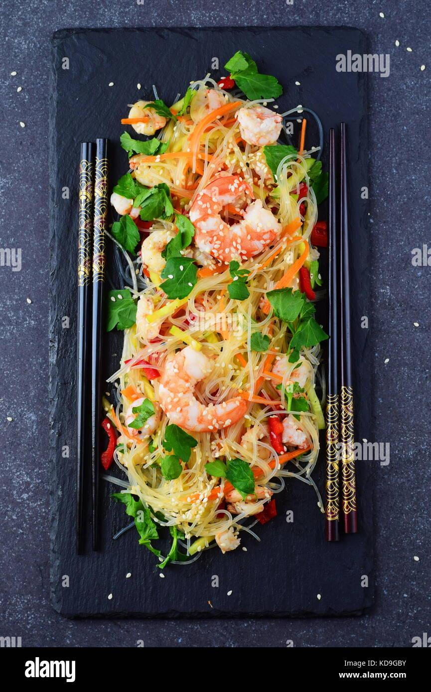 Fideos con gambas y verduras en una placa de piedra negra sobre un fondo gris abstracto concepto de comida saludable. Foto de stock