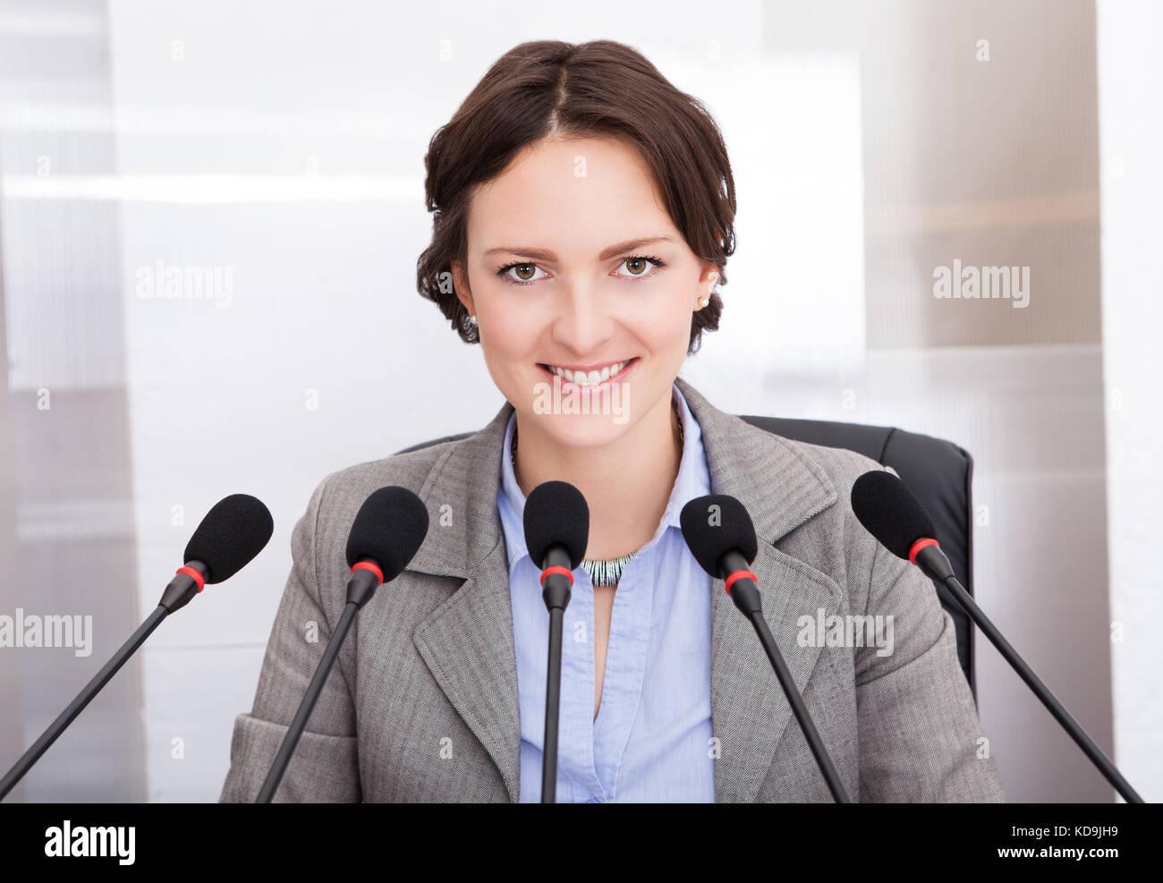 La empresaria sonriente sosteniendo el papel hablando delante de varios micrófonos Imagen De Stock