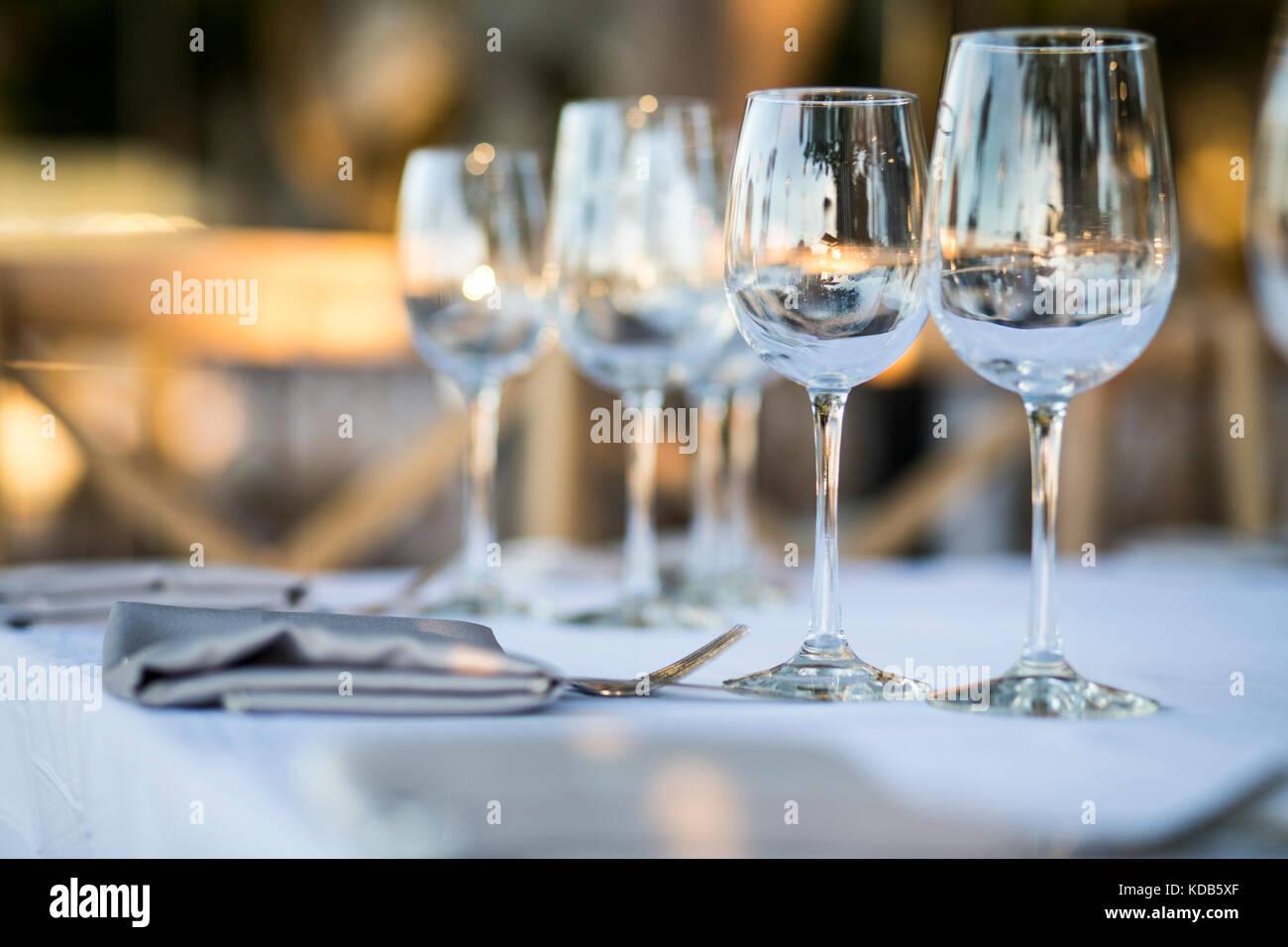 Configuración de la tabla de lujo para cenar con y cristalería, hermoso fondo borroso. Preparación Imagen De Stock