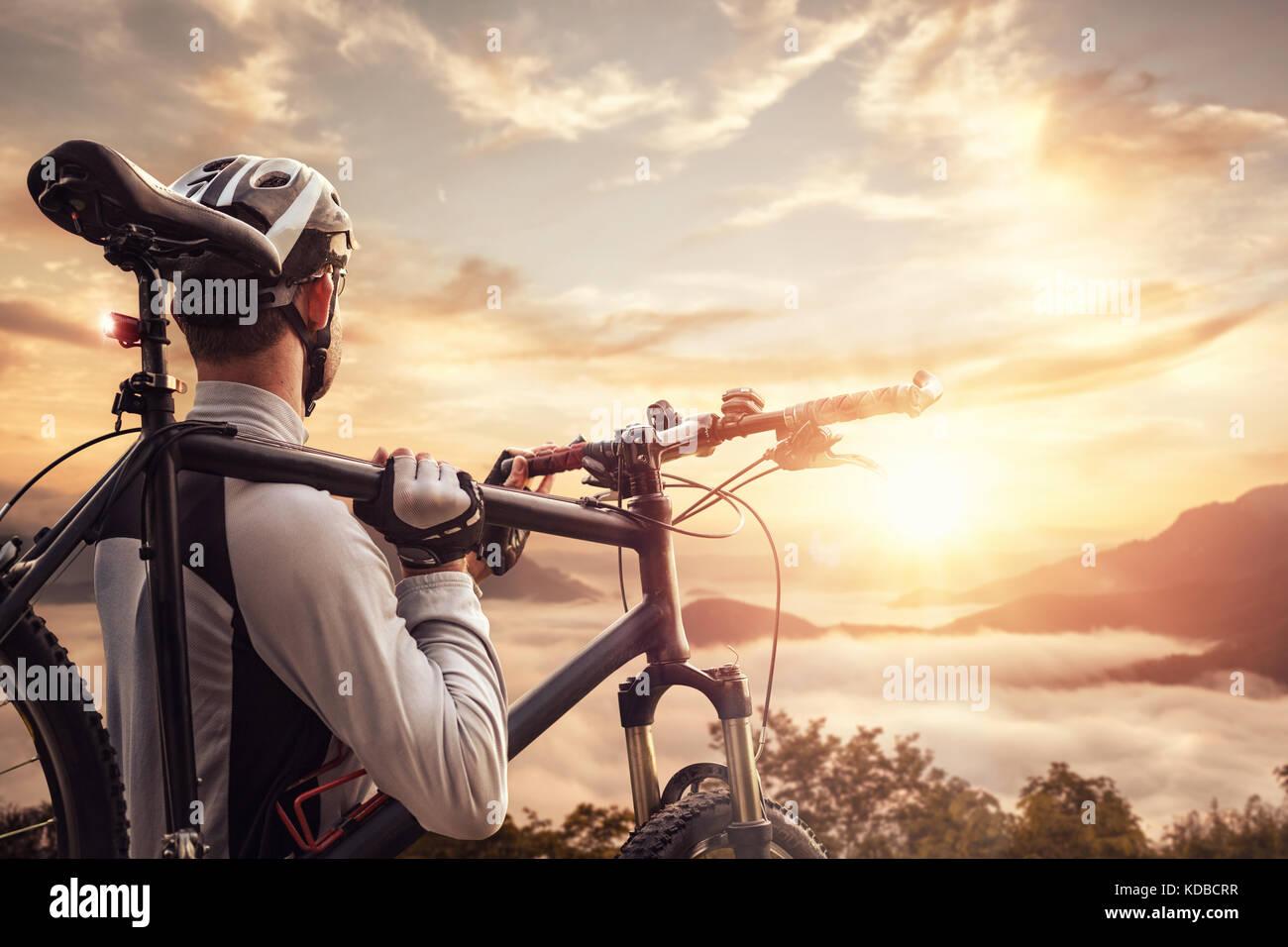 Ciclista de montaña con vistas a un valle al atardecer Imagen De Stock