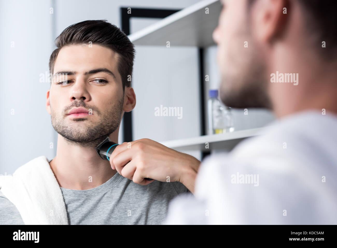 El hombre se afeita con recortador eléctrico Imagen De Stock