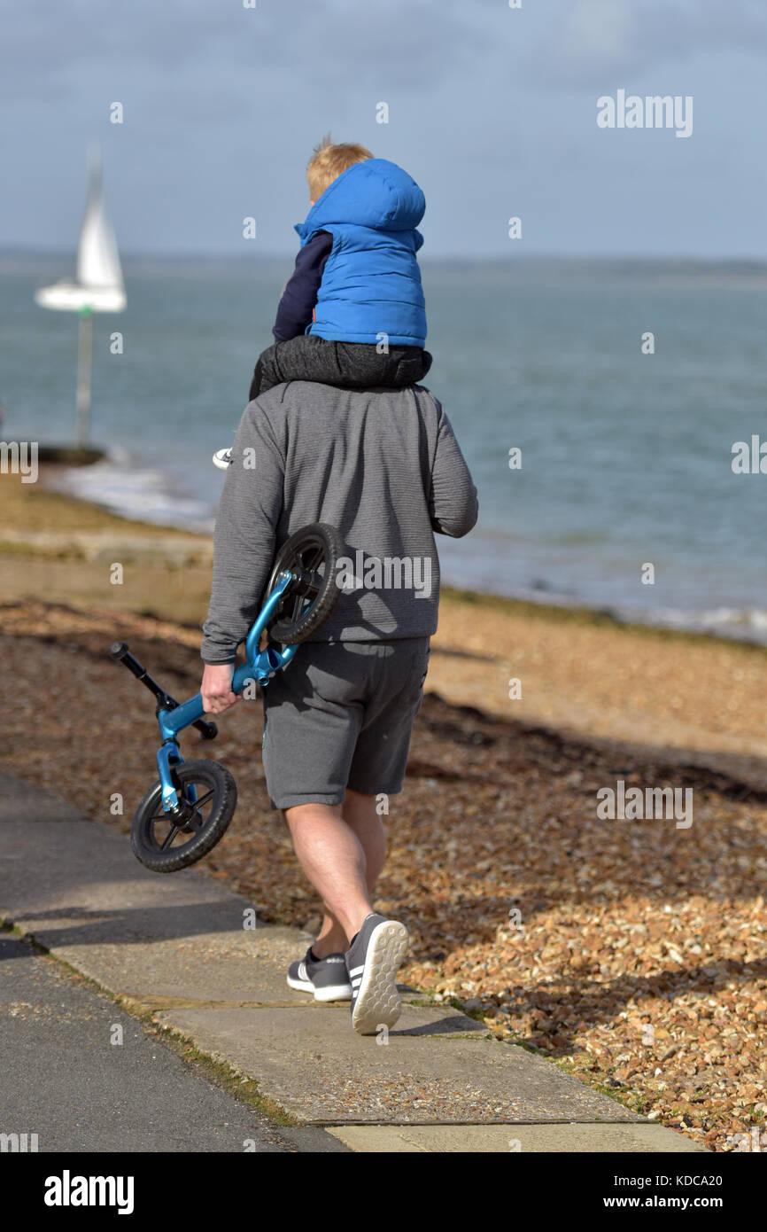 Un hombre caminando por el paseo marítimo con un niño pequeño sobre sus hombros llevando un scooter Imagen De Stock