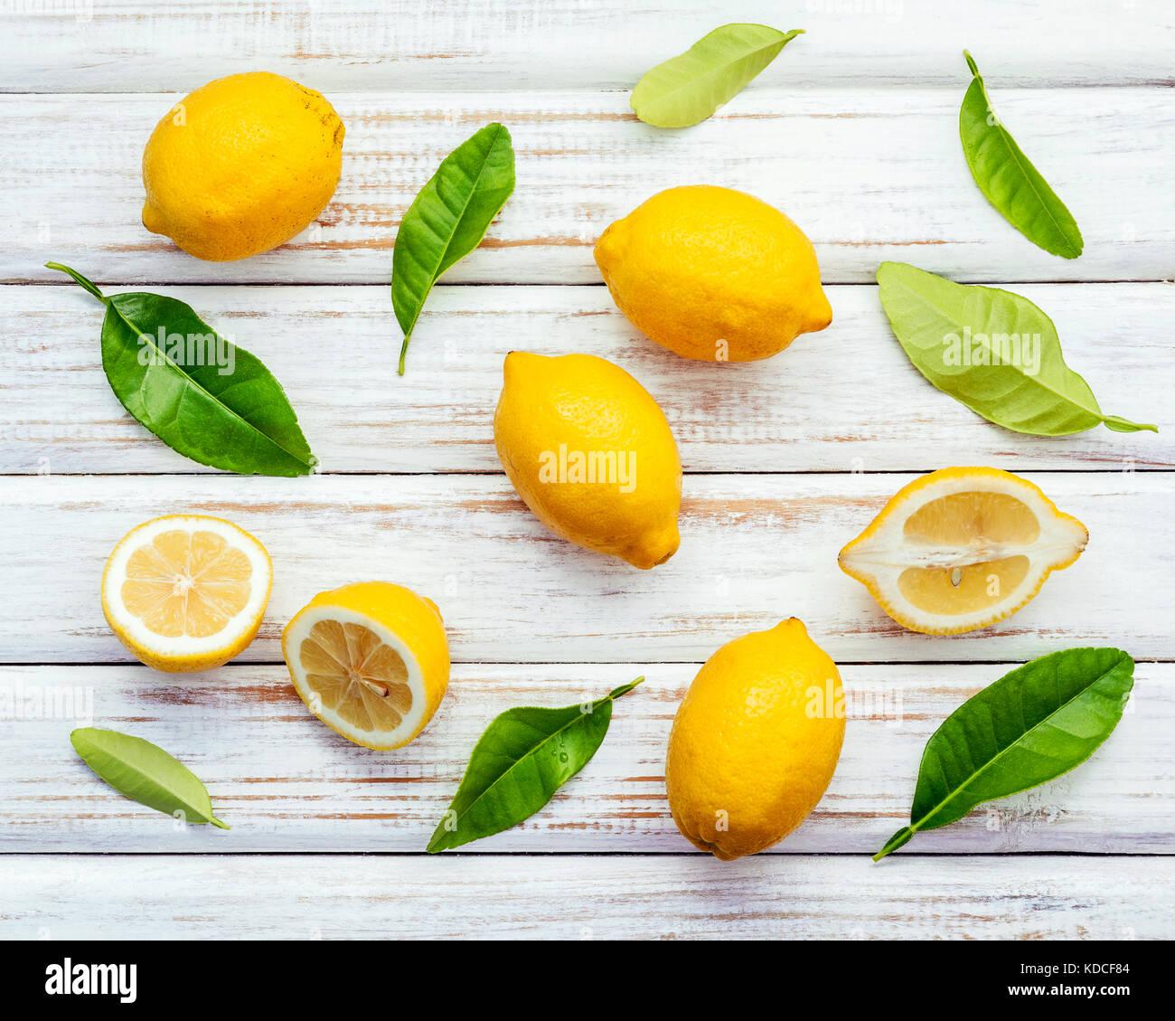 Limones frescos y limones hojas sobre fondo de madera rústica. limones frescos y la rodaja de limón sobre mesa de Foto de stock