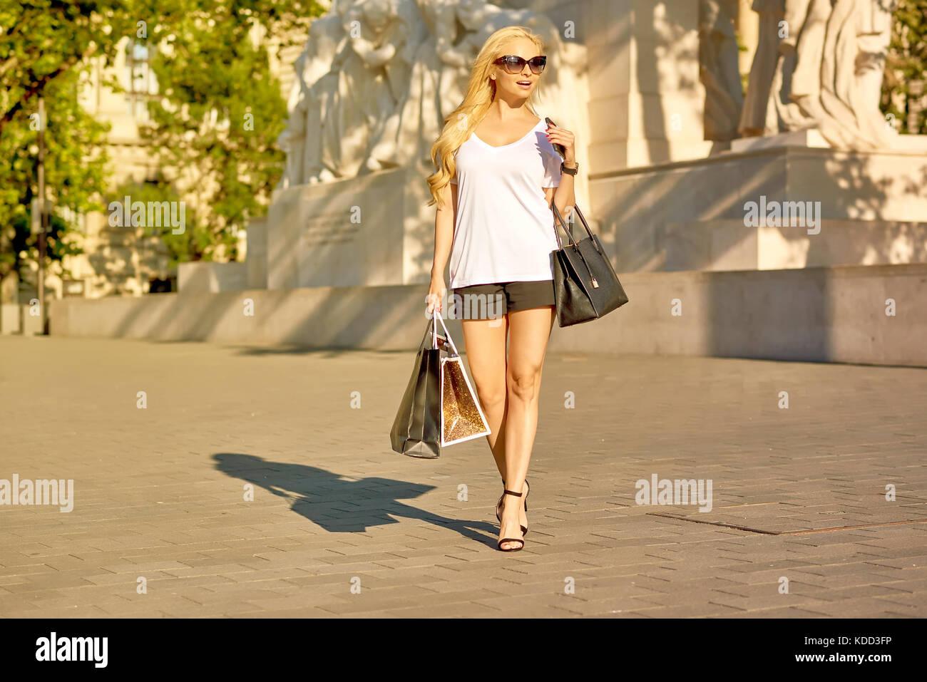2a6d002864d5 Una joven y bella mujer rubia caminando sobre un cuadrado en tacones altos  en el atardecer