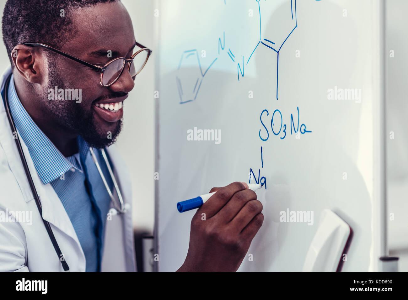 Emocionado trabajador médico afroamericano DIBUJO dibujo química Foto de stock