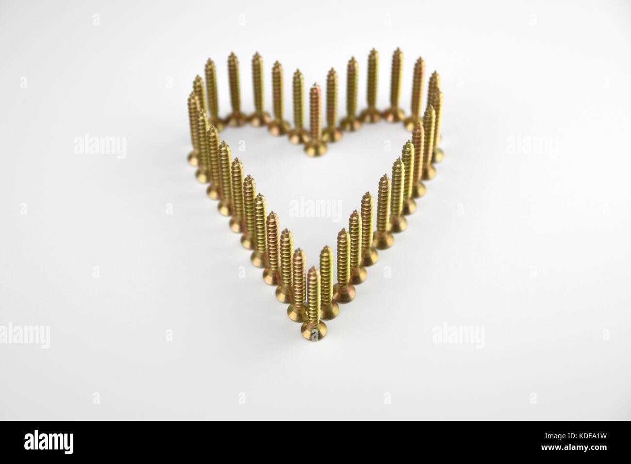 Amor corazón de tornillos de latón permanente sobre fondo blanco. Imagen De Stock