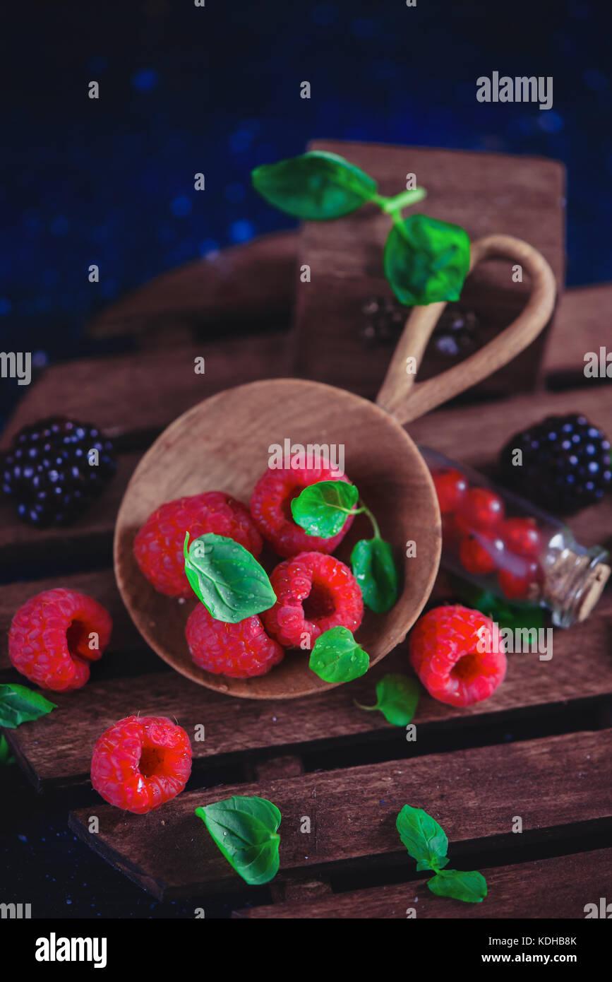 Pequeño recipiente de madera con frambuesas frescas y hojas de menta. Fotografía de alimentos oscuro con Imagen De Stock