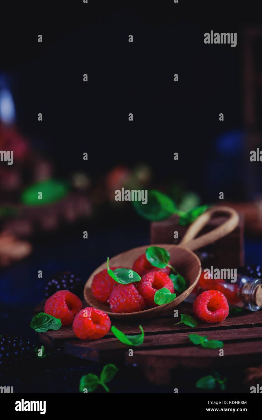 Las bayas surtidas en una placa de madera sierva. frambuesas y moras con hojas de menta verde oscura fotografía Imagen De Stock