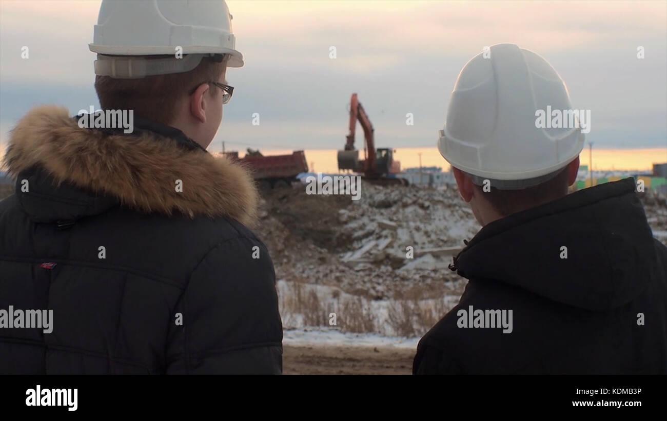 Vista posterior de arquitectos inspección obra. Dos ingenieros en sombreros duros en obras de construcción Imagen De Stock