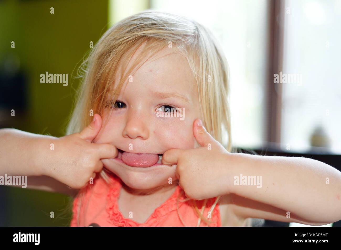 Una niña de tres años tirando de caras Foto de stock
