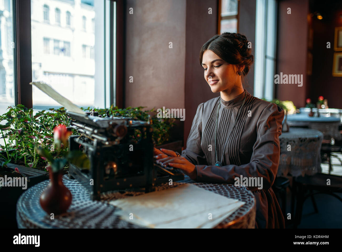 6df40fd0a ... el perfil de la bella joven en el café con la antigua máquina de  escribir. mujer sonriente e imprime algo en vintage cafe. cabello oscuro niña  sentada