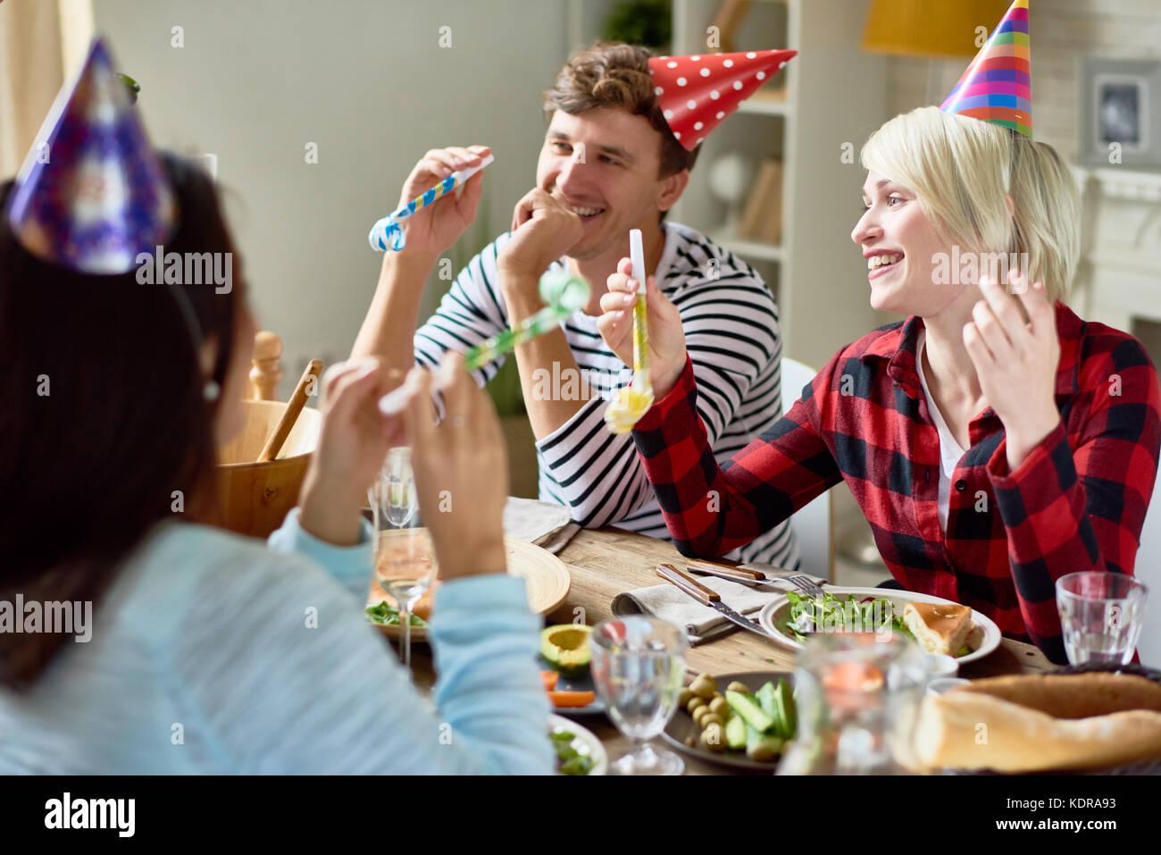 Las parejas felices celebrando el cumpleaños de mesa durante la cena. Imagen De Stock
