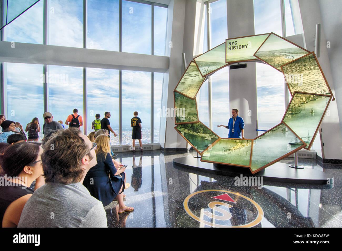 Un guía turístico, educa a los turistas visitantes sobre la historia de la ciudad de Nueva York en un observatorio mundial, en el World Trade Center, New York, NY, EE.UU. Foto de stock