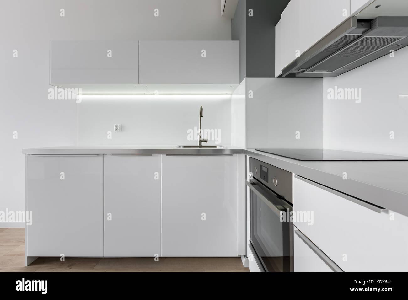 Cocina moderna con muebles blancos, encimera, fregadero, horno y ...
