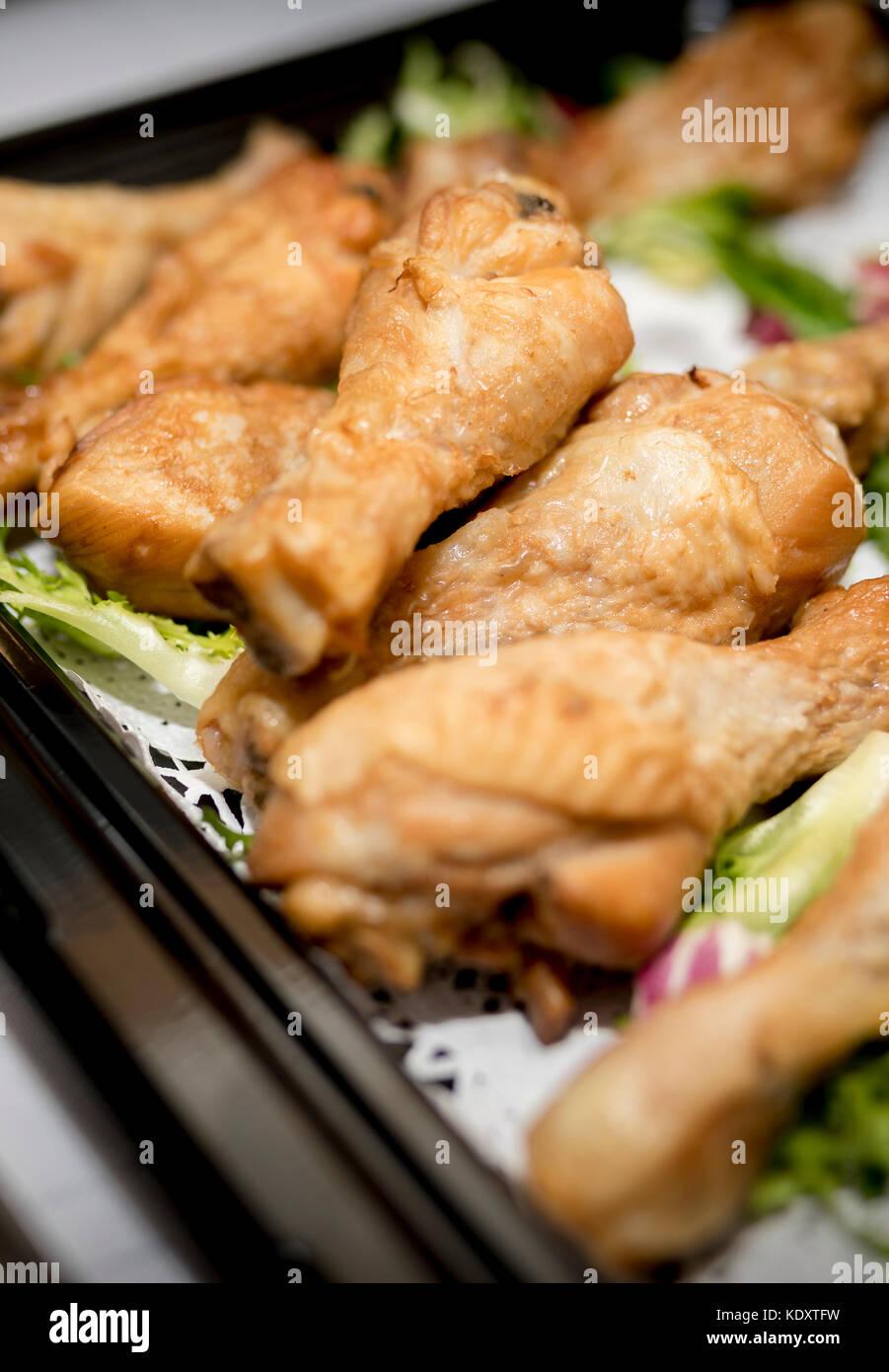 Cerca de palillos de tambor de pollo asado en un buffet en una bandeja negra con lechuga como guarnición Foto de stock