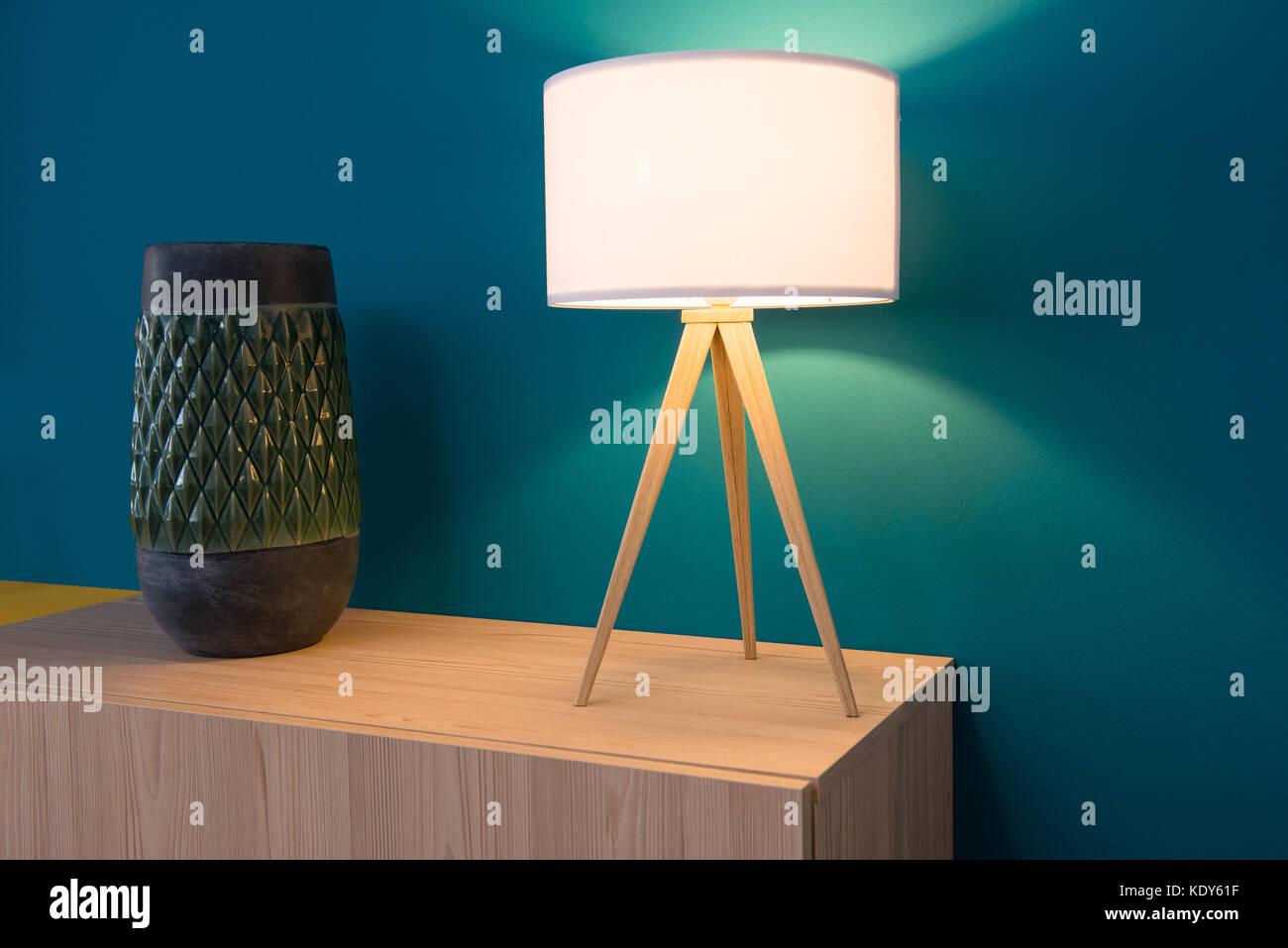 Lámpara y armario jarrón de pared azul en segundo plano. Imagen De Stock