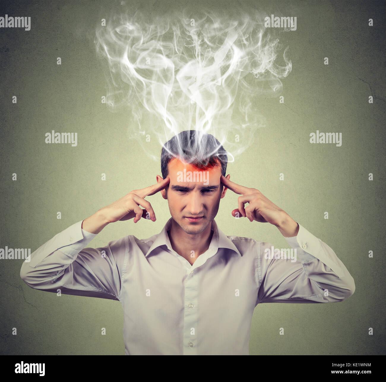 El hombre piensa muy intensamente tener dolor de cabeza aislado sobre la pared gris de fondo expresión de cara Imagen De Stock