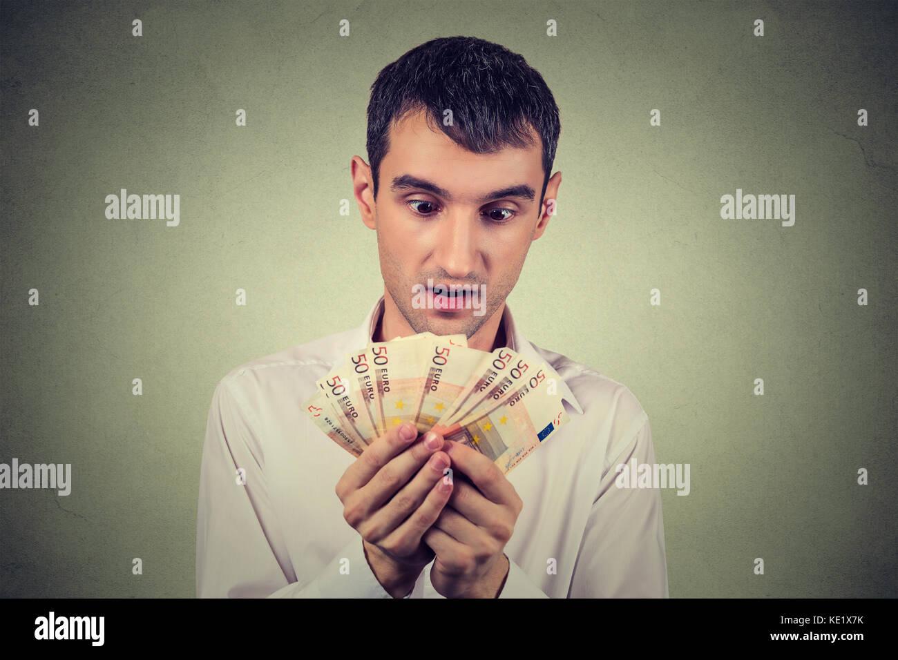 Joven Hombre de negocios codicioso contando dinero Imagen De Stock