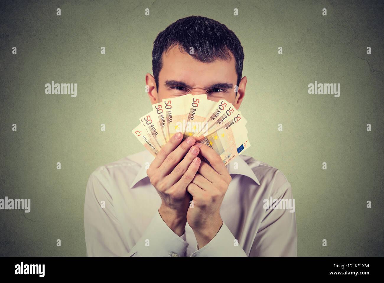 Hombre codicioso con billetes billetes aislado sobre fondo de pared gris Imagen De Stock