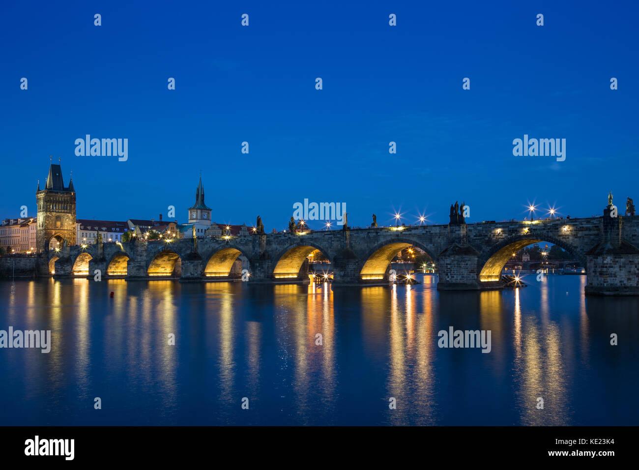 Iluminado el puente de Carlos (Karluv Most) y edificios antiguos en el casco antiguo de la ciudad y de sus reflexiones Imagen De Stock