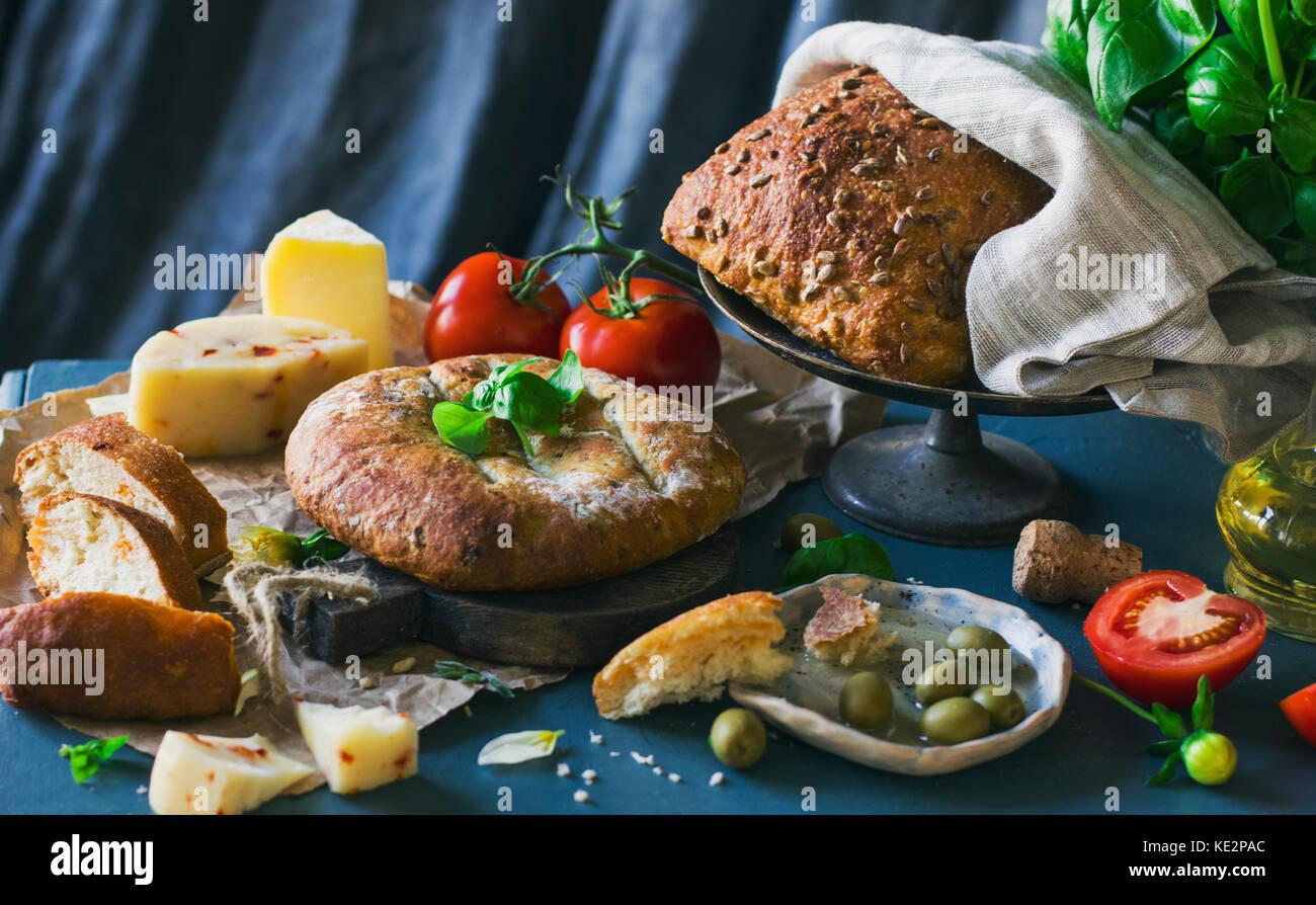 Pan de grano, queso y tomates sobre fondo azul. Foto de stock