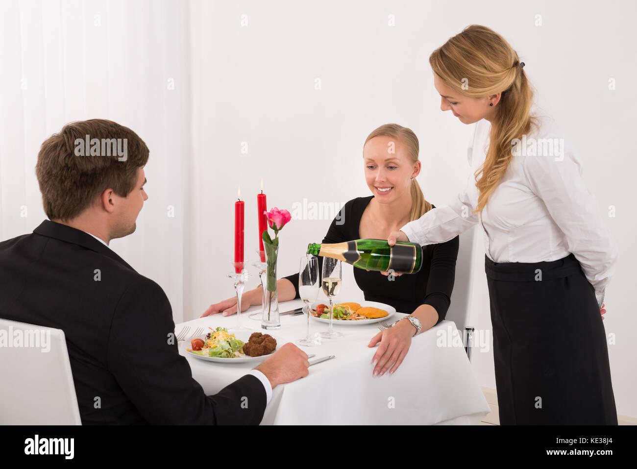 Camarera de verter en el vaso de champagne para la joven pareja en restaurante. Imagen De Stock