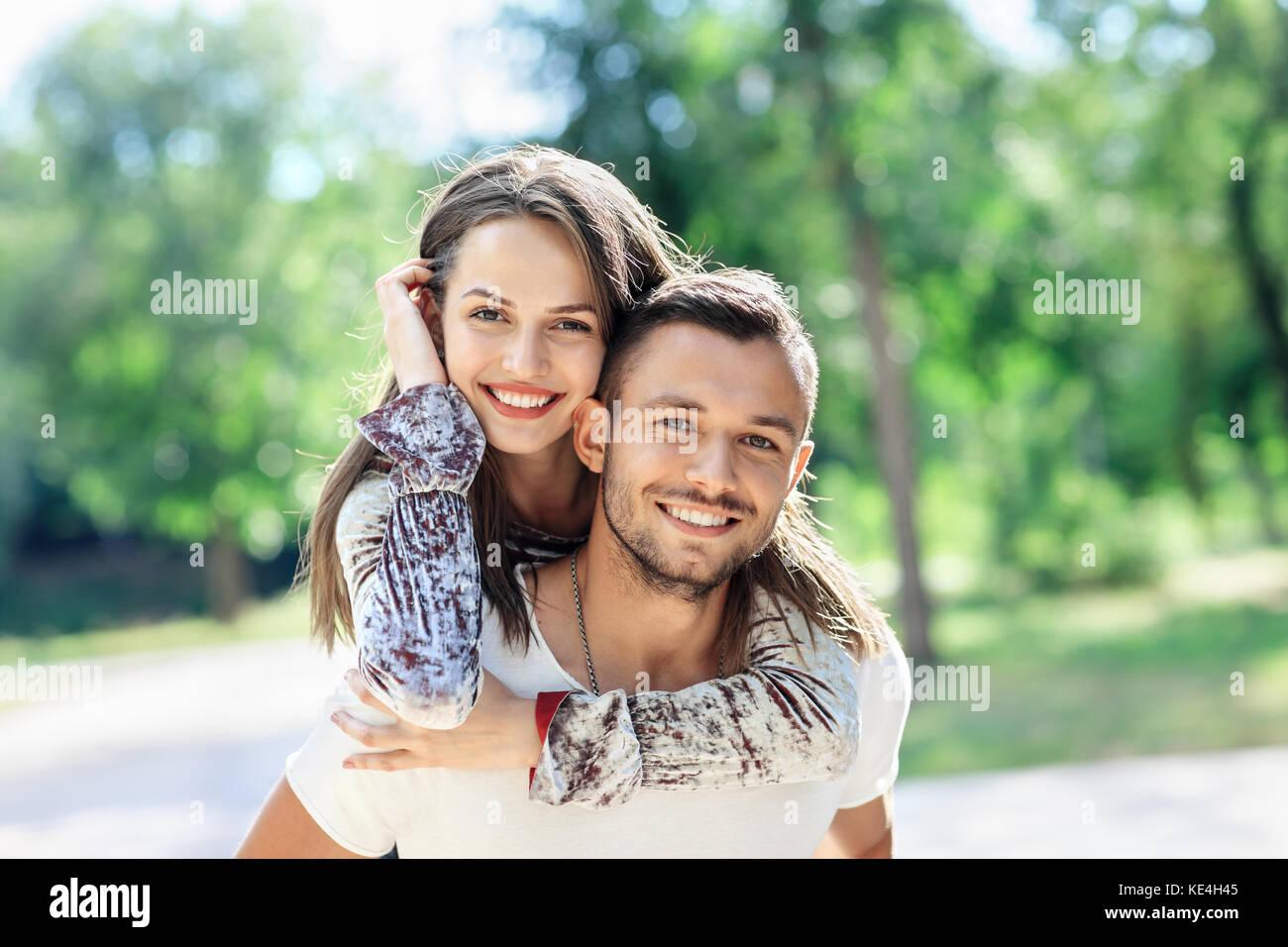 Los amantes al aire libre retrato de un hombre y una mujer joven feliz mirando a la cámara. Chica sonriente piggyback Foto de stock