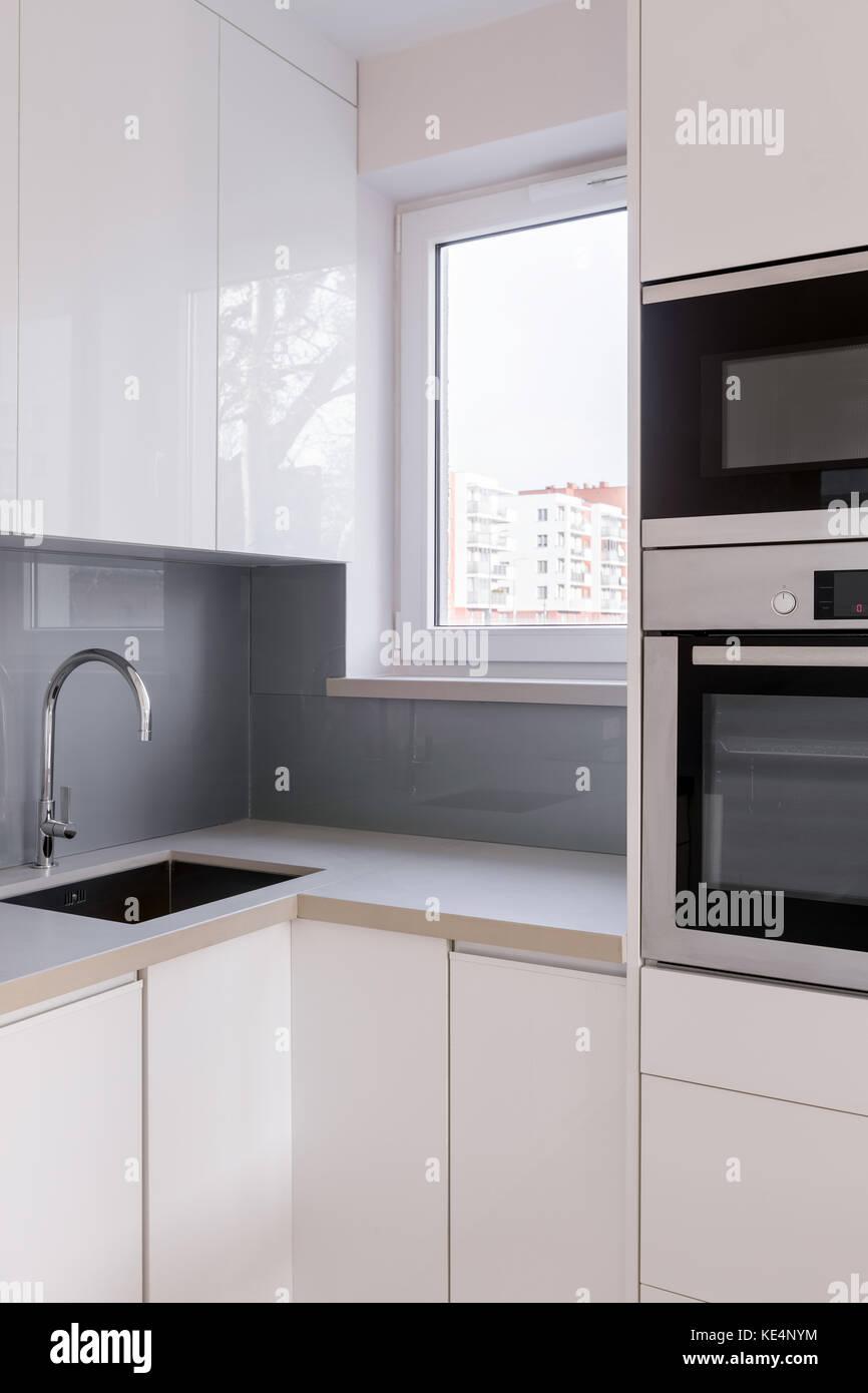 Cocina con muebles blancos, fregadero y encimera de azulejos grises ...