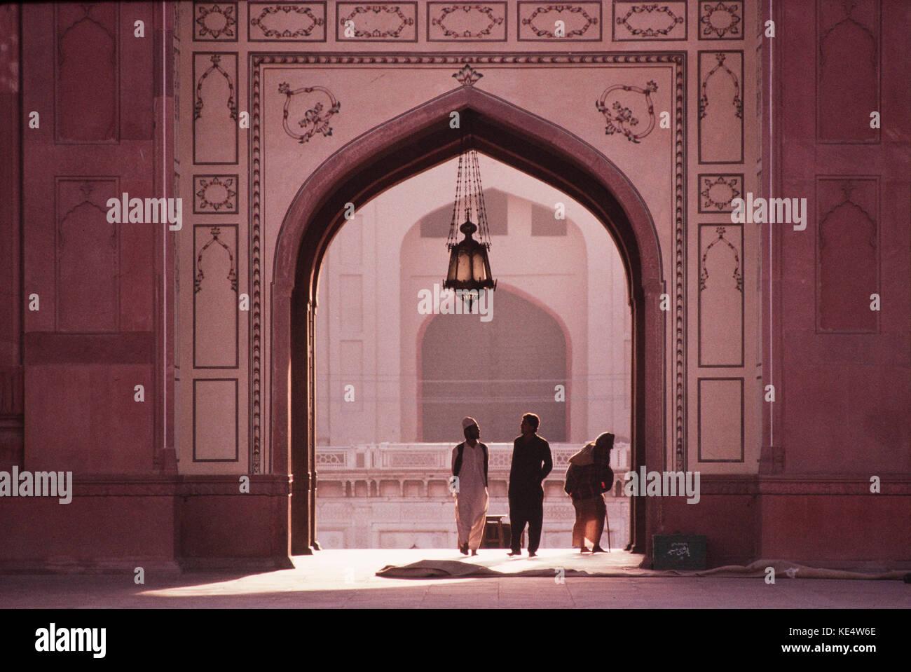 La gente que viene a través de la entrada principal de la Mezquita Badshahi en Lahore, Pakistán. Foto de stock