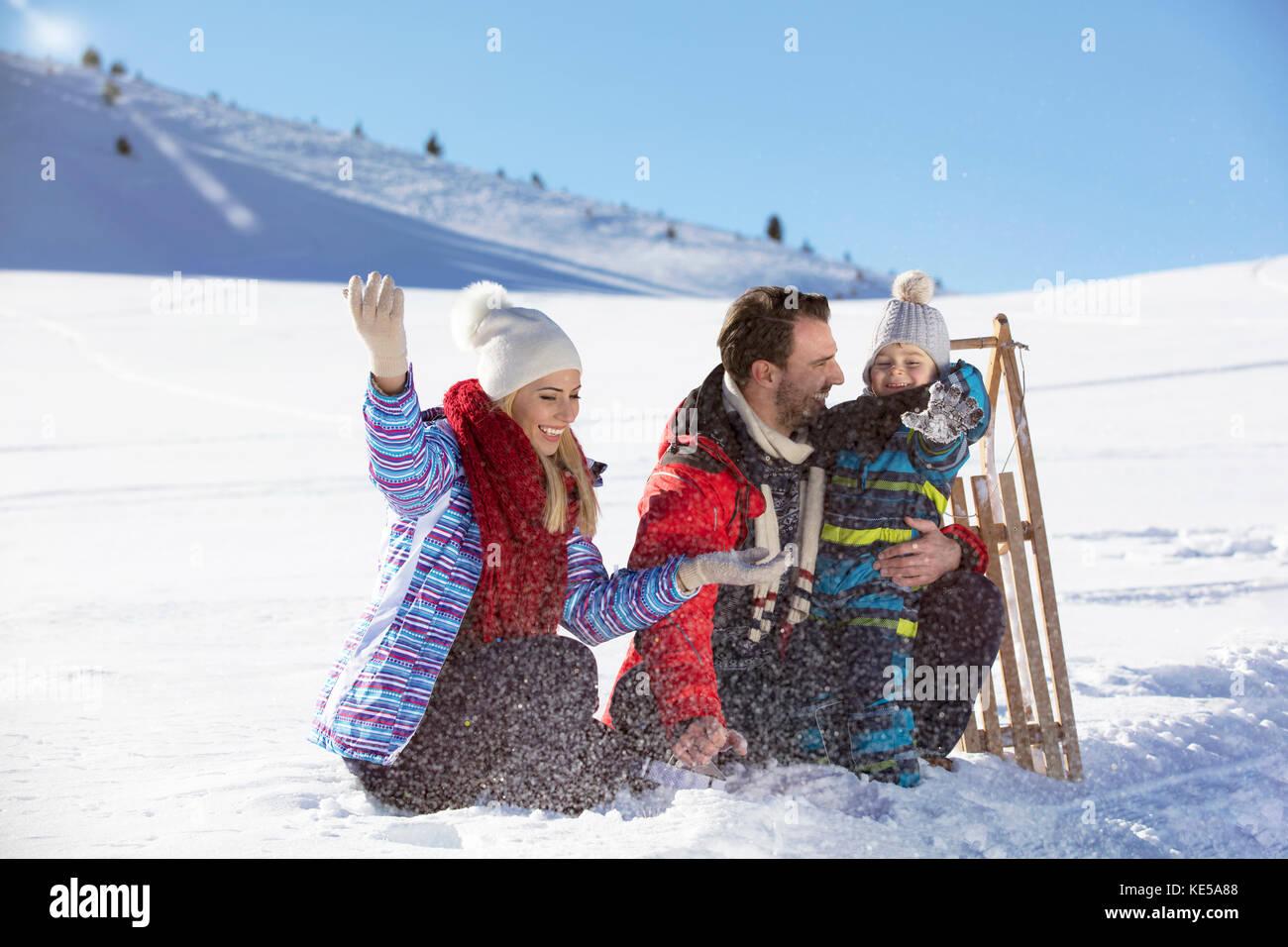 Los paseos en familia feliz el patín en el invierno la madera, alegres entretenimientos de invierno Imagen De Stock