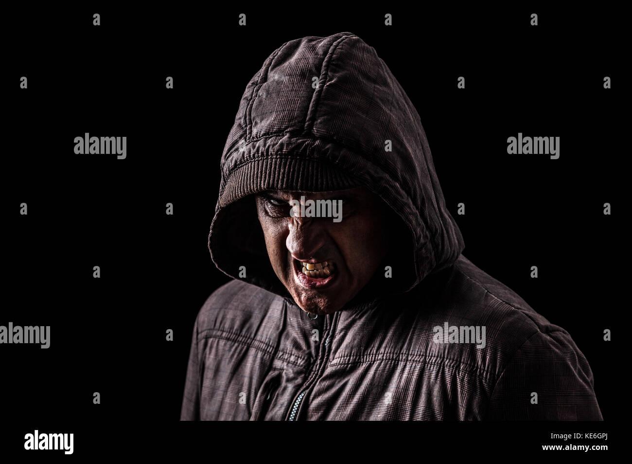 Muy enojado, agresivo, raro hombre ocultando las sombras, de pie en la oscuridad.fondo negro / creepy peligroso Imagen De Stock