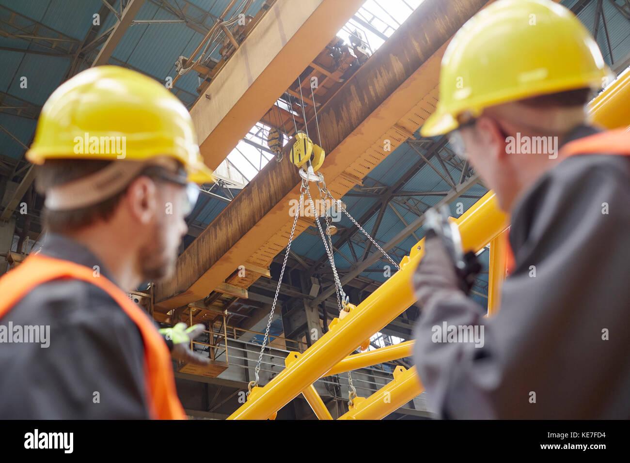 Trabajador masculino utilizando un walkie-talkie para guiar la grúa hidráulica bajada del equipo en la Imagen De Stock