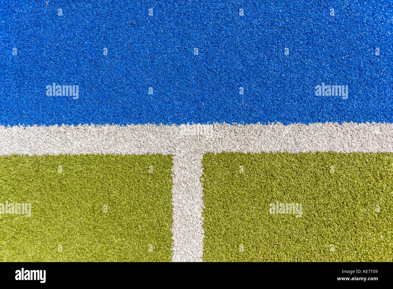 https://c8.alamy.com/compes/ke7t09/deportes-campo-de-cesped-sintetico-astro-closeup-limite-linea-blanca-con-detalles-verdes-y-azules-ke7t09.jpg