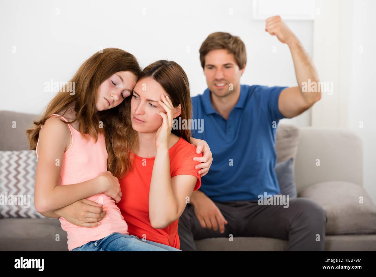 Depresiva madre e hija delante del padre violento sentado en el sofá Imagen De Stock